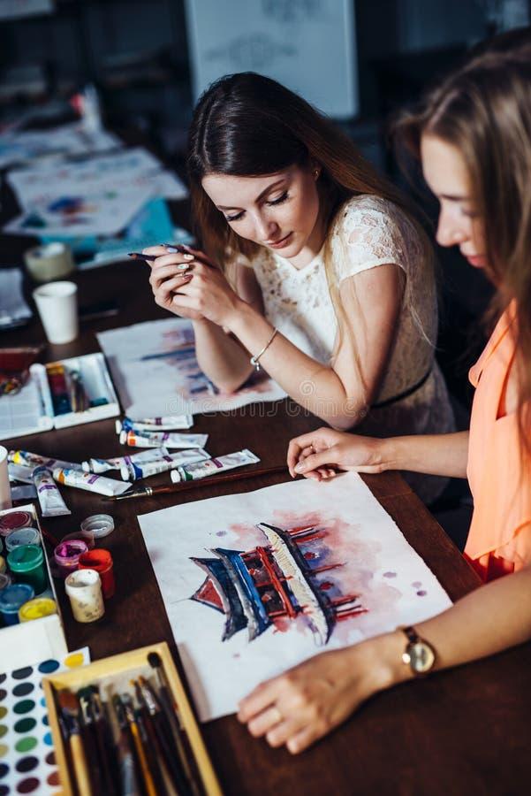 Duas jovens mulheres que atendem à pintura do aquarelle classificam para adultos na escola de arte Uma menina que mostra sua arte imagem de stock royalty free