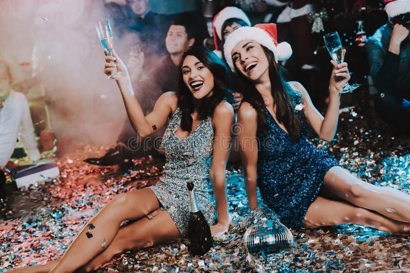 Duas jovens mulheres que comemoram o ano novo no partido foto de stock