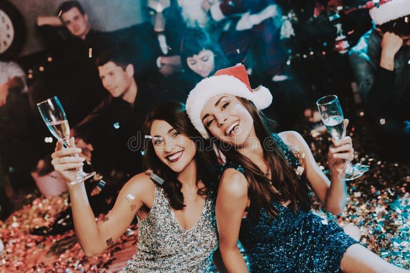 Duas jovens mulheres que comemoram o ano novo no partido imagem de stock