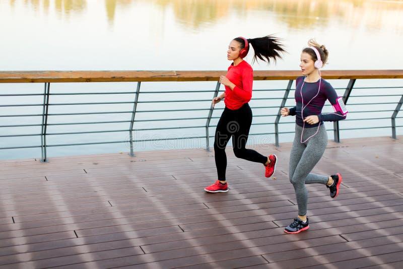 Duas jovens mulheres que correm pelo rio imagem de stock