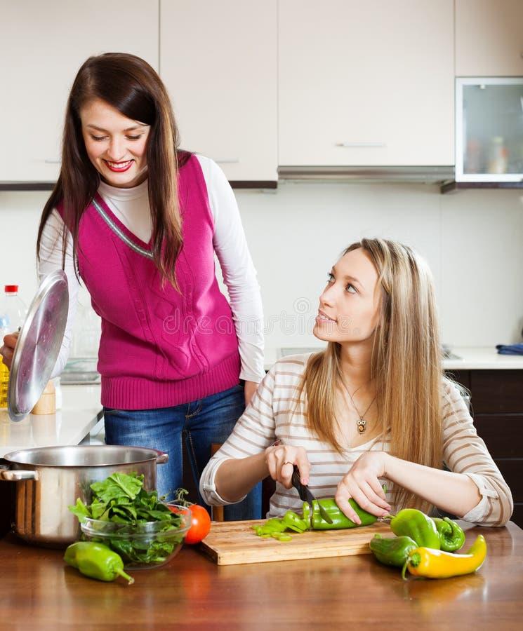 Duas jovens mulheres que cozinham junto foto de stock royalty free