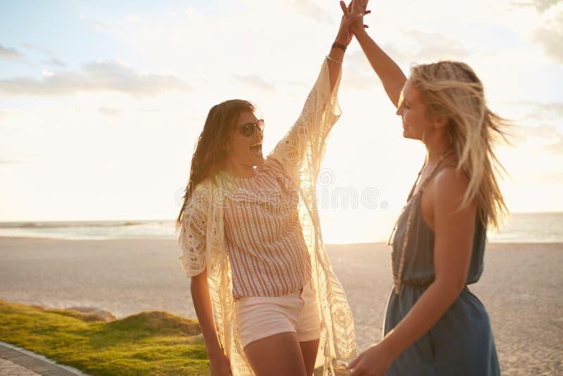 Duas jovens mulheres que dão a elevação cinco na praia fotos de stock royalty free