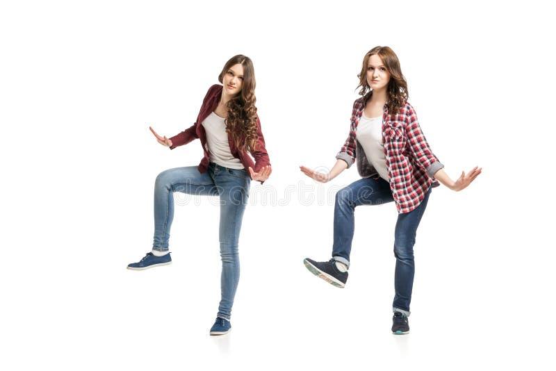 Duas jovens mulheres que dançam sobre o fundo branco fotografia de stock royalty free