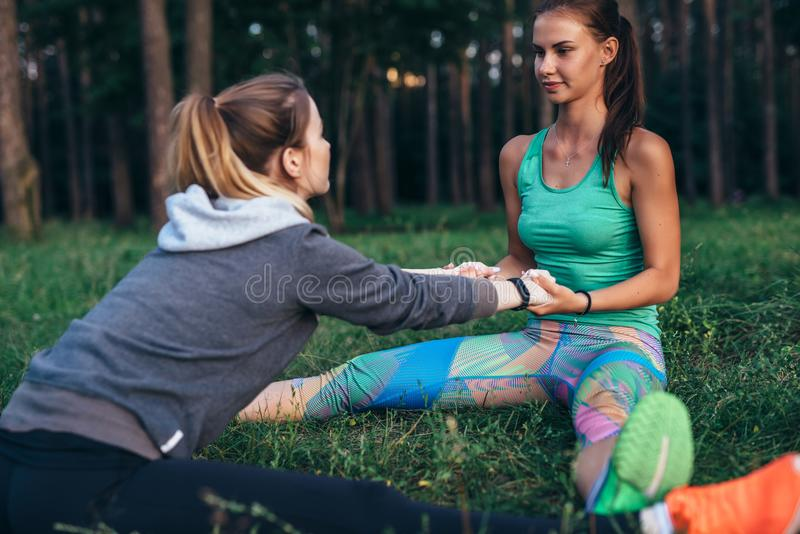 Duas jovens mulheres que executam a ioga do sócio levantam, straddle assentado dobro, esticando seus pé e músculos traseiros que  foto de stock royalty free