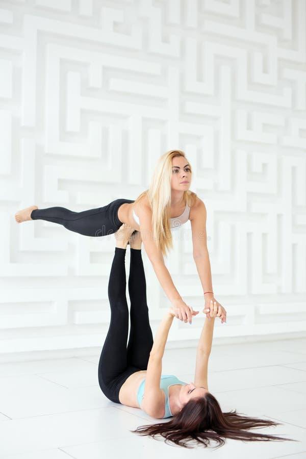 Duas jovens mulheres que fazem a ioga do acro do equilíbrio no estúdio branco fotos de stock royalty free