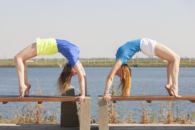 Duas jovens mulheres que fazem a ioga na natureza Aptid?o, esporte, ioga e conceito saud?vel do estilo de vida foto de stock