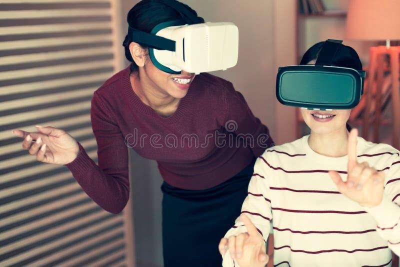 Duas jovens mulheres que jogam com auriculares e riso de VR imagens de stock royalty free
