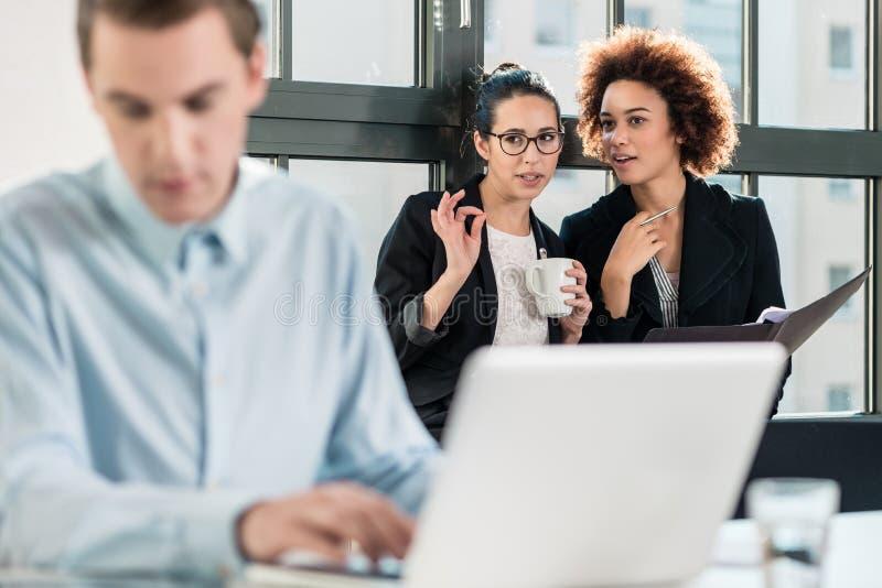 Duas jovens mulheres que riem atrás de seu colega masculino foto de stock