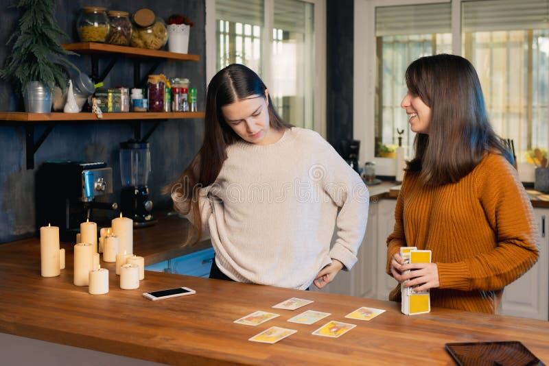 Duas jovens mulheres que saem do convés das cartas de tarot numa cozinha foto de stock