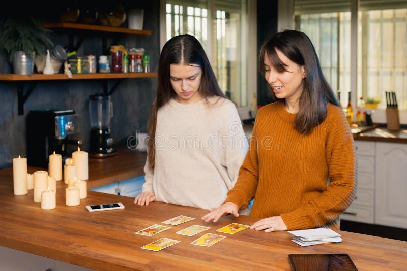 Duas jovens mulheres que saem do convés das cartas de tarot numa cozinha Velas e dispositivos móveis presentes fotografia de stock royalty free