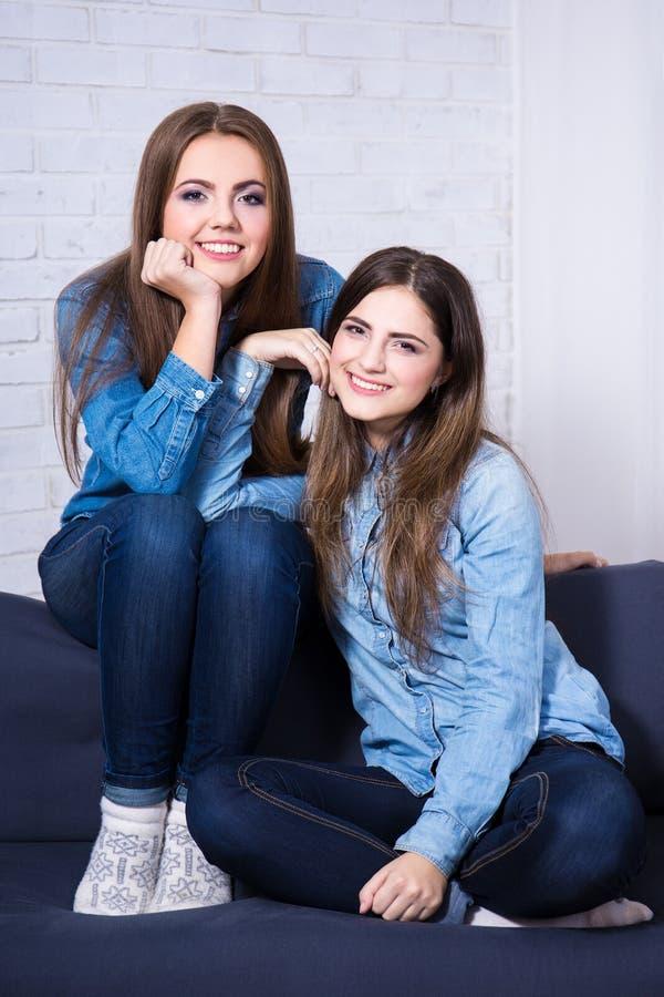 Duas jovens mulheres que sentam-se no sofá na sala de visitas fotos de stock royalty free