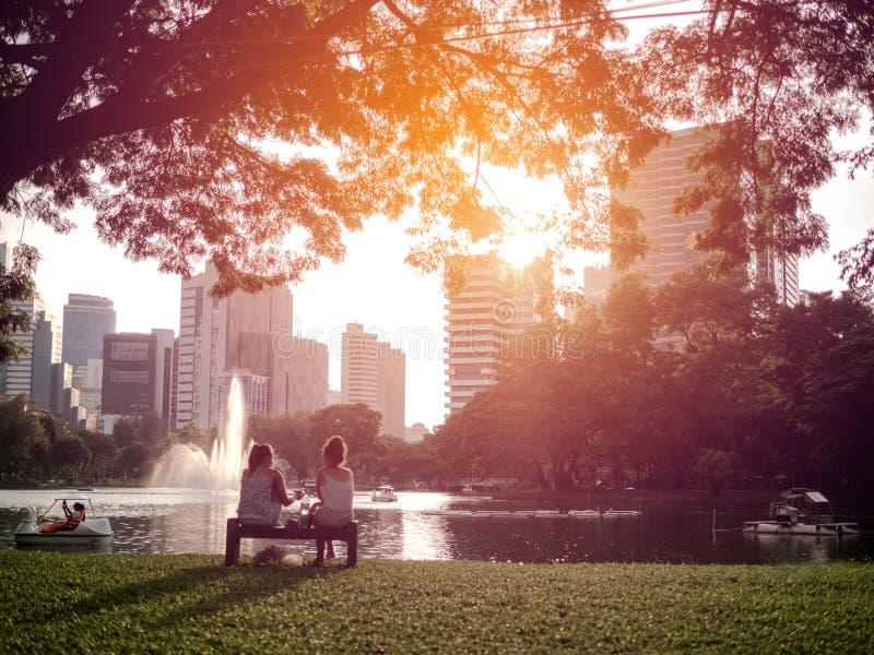 Duas jovens mulheres que sentam-se sob uma árvore grande em um parque foto de stock royalty free