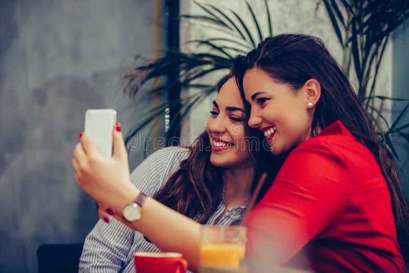 Duas jovens mulheres que têm o divertimento no café e que tomam o selfie com smartphone imagens de stock royalty free