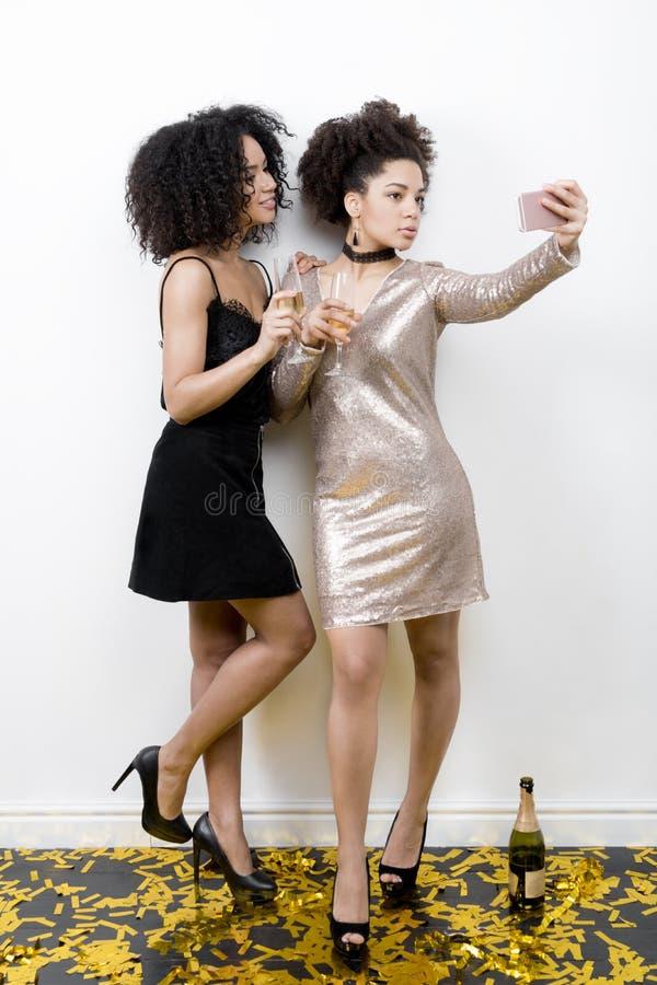 Duas jovens mulheres que tomam o partido do autorretrato em casa fotografia de stock