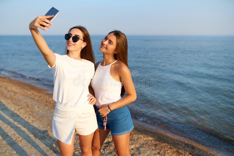Duas jovens mulheres que tomam um selfie na praia com uma opini?o do mar Os amigos est?o sorrindo olhando a c?mera Vestir das men imagens de stock
