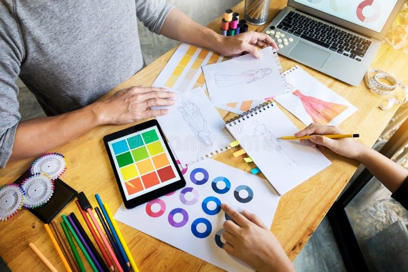 duas jovens mulheres que trabalham como desenhadores de moda e o sketche de tiragem fotos de stock royalty free