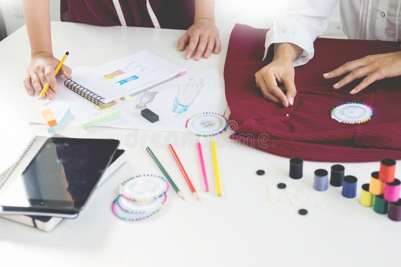 duas jovens mulheres que trabalham como desenhadores de moda e o sketche de tiragem fotos de stock