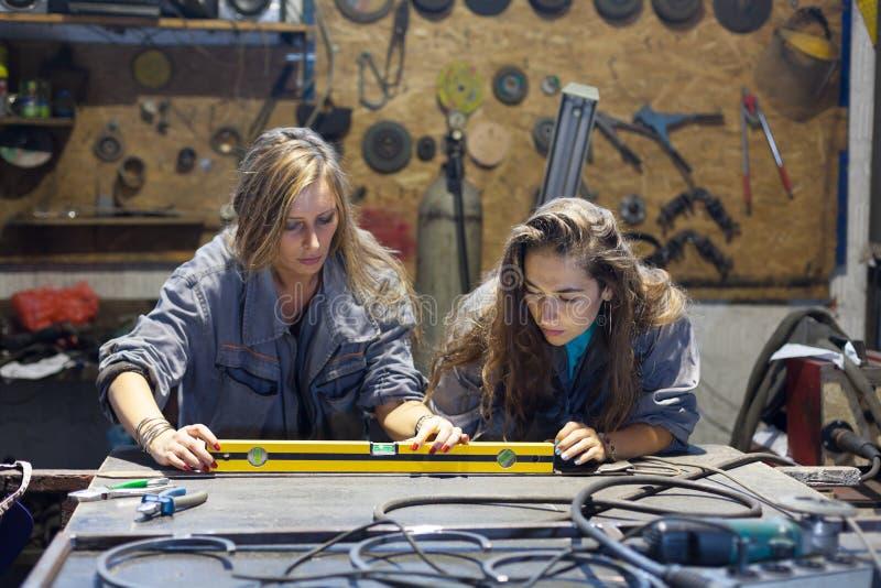 duas jovens mulheres que trabalham em uma loja do mecânico fotos de stock royalty free