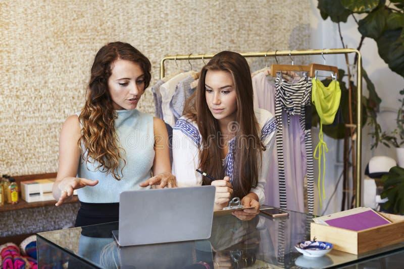 Duas jovens mulheres que trabalham na loja de roupa imagem de stock