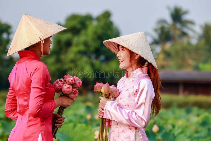 Duas jovens mulheres que vestem um vestido vietnamiano foto de stock