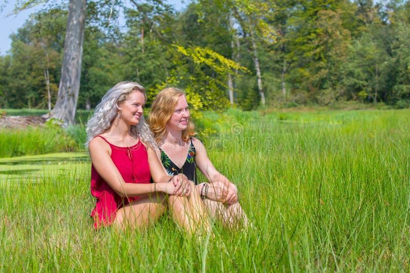 Duas jovens mulheres sentam-se junto na natureza fotografia de stock royalty free