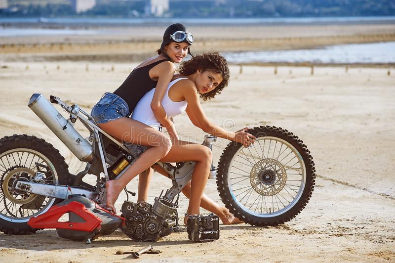 Duas jovens mulheres têm o divertimento que joga em uma motocicleta desmontada imagem de stock