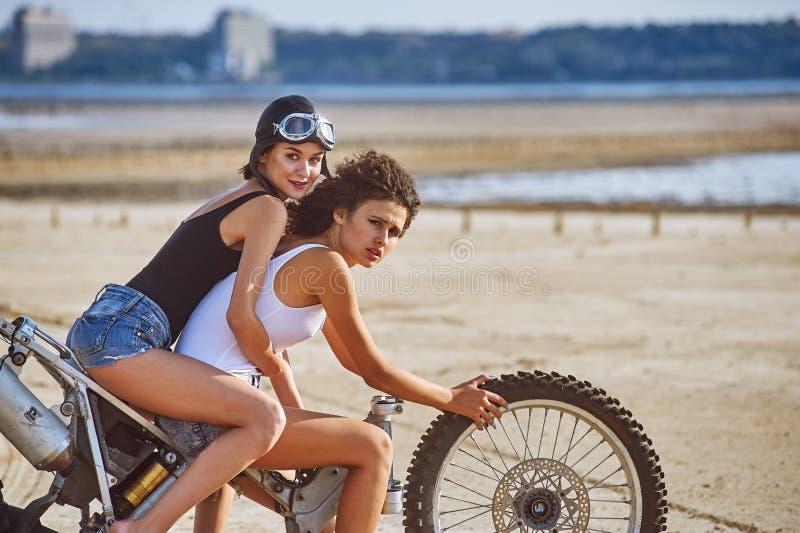 Duas jovens mulheres têm o divertimento que joga em uma motocicleta desmontada imagem de stock royalty free