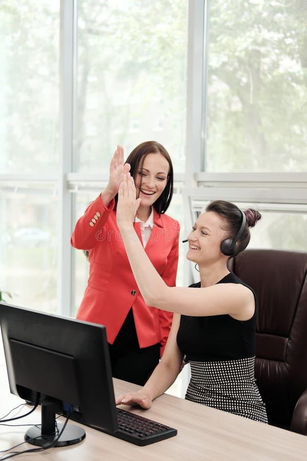 Duas jovens mulheres trabalham em um escritório brilhante no computador Discuta trabalhos e aprecie um negócio bem sucedido cabe? fotos de stock