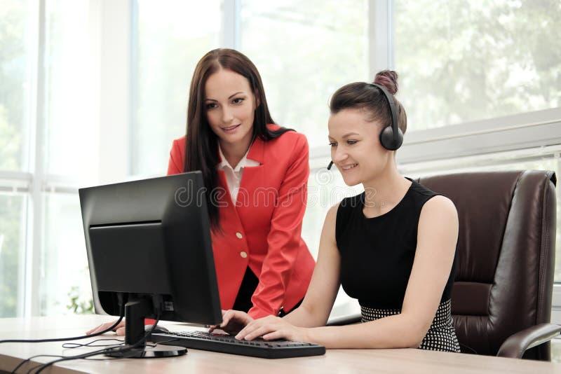 Duas jovens mulheres trabalham em um escritório brilhante no computador Discuta trabalhos e aprecie um negócio bem sucedido cabe? fotografia de stock