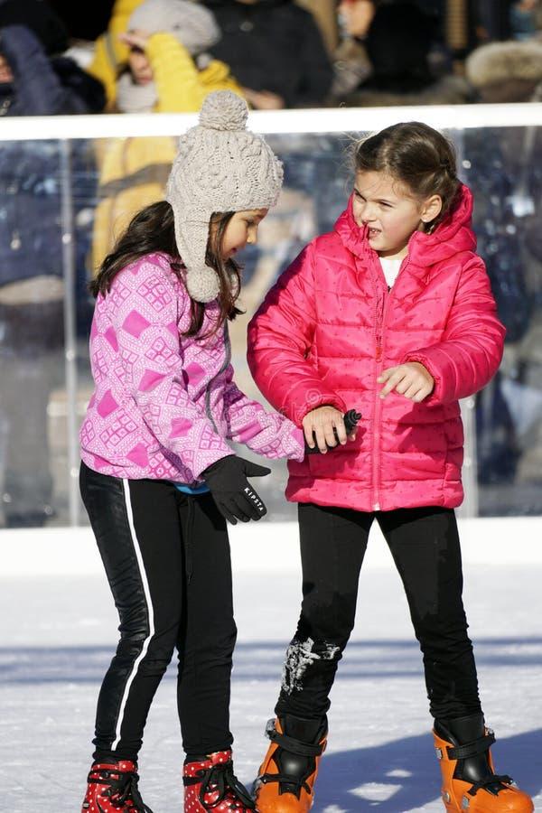 Duas jovens raparigas a patinar ao ar livre num dia quente de inverno imagens de stock
