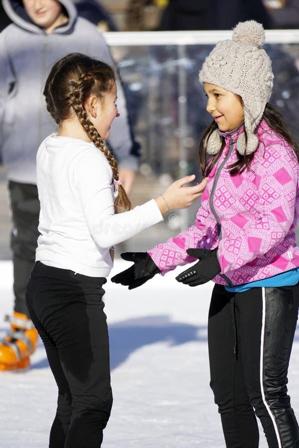Duas jovens raparigas a patinar ao ar livre num dia quente de inverno imagens de stock royalty free