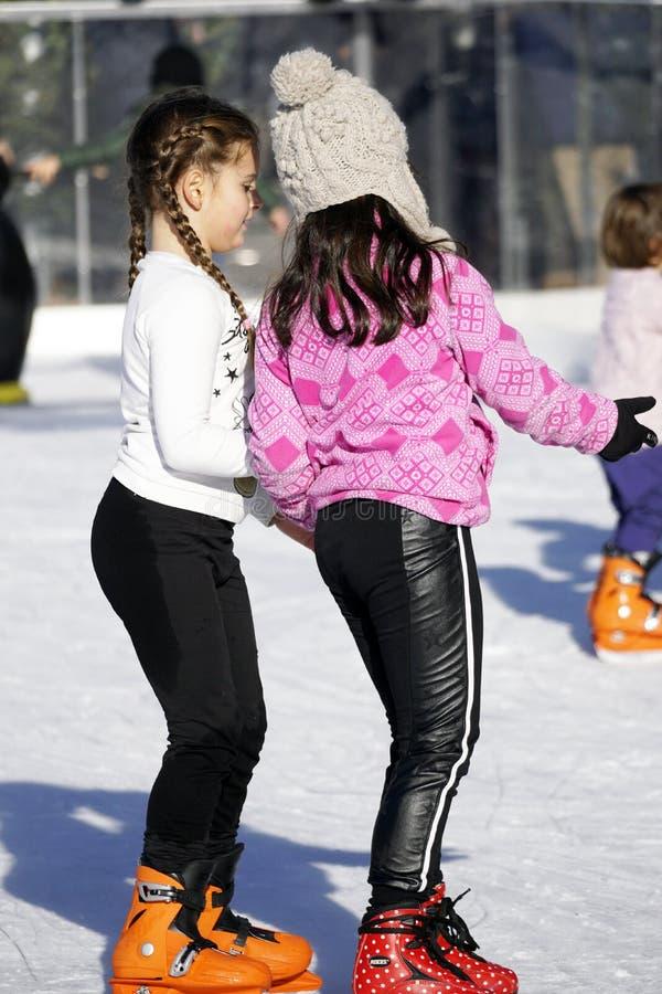Duas jovens raparigas a patinar ao ar livre num dia quente de inverno fotos de stock royalty free