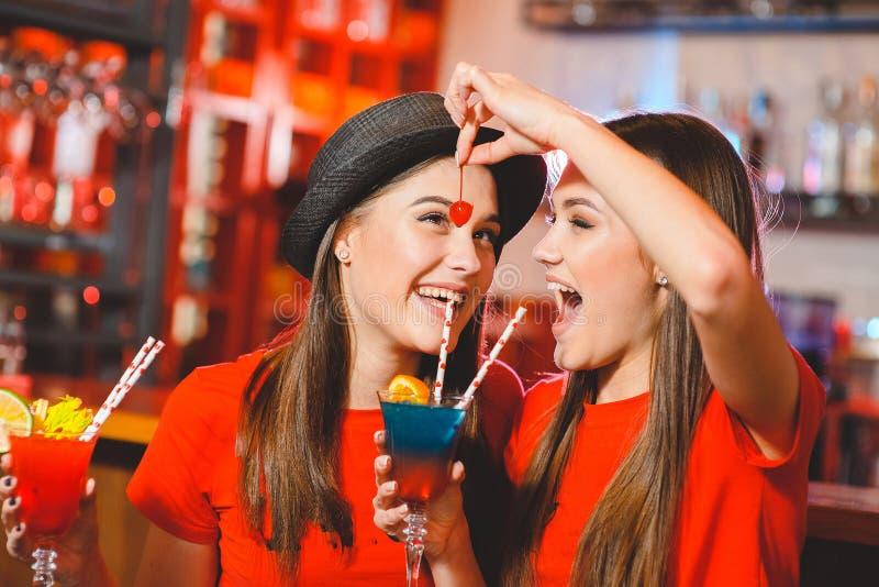 Duas lésbica das moças em um partido no clube estão guardando cerejas do cocktail foto de stock