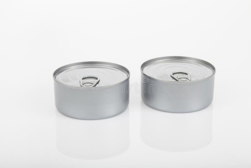 Duas latas do atum no fundo branco fotografia de stock