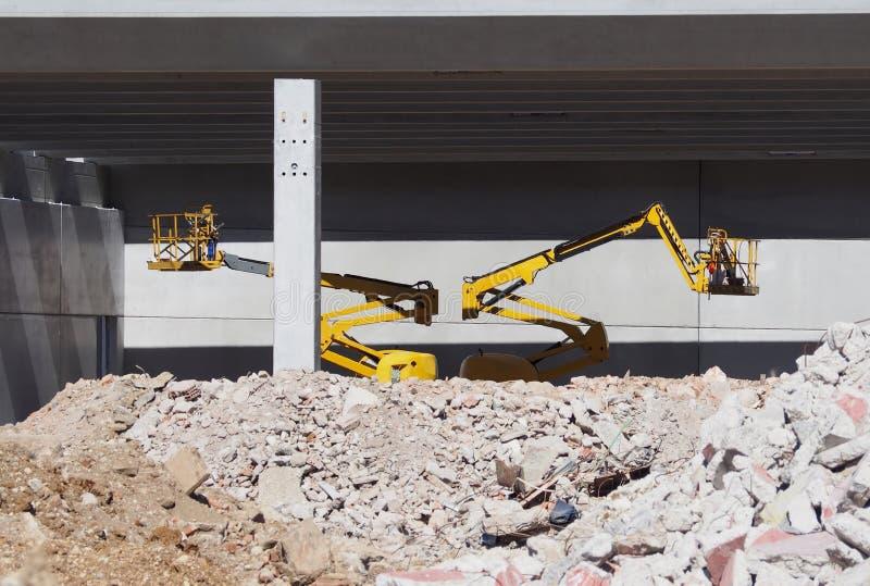 Duas máquinas desbastadoras da cereja dentro de uma construção concreta sob a construção atrás de um grande montão dos restos Nen imagens de stock