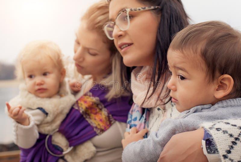 Duas mães com os bebês na urdidura dos portadores de bebê imagens de stock