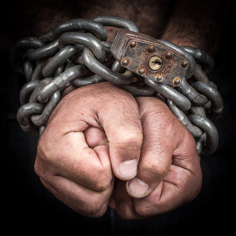 Duas mãos acorrentadas com uma corrente do ferro e um cadeado imagens de stock