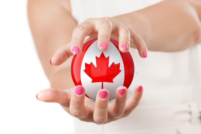 Duas mãos da mulher que protegem a esfera canadense do globo da terra da bandeira imagem de stock royalty free