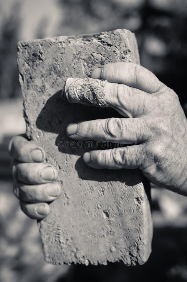 Duas mãos do homem idoso que guardam o tijolo velho dentro imagens de stock