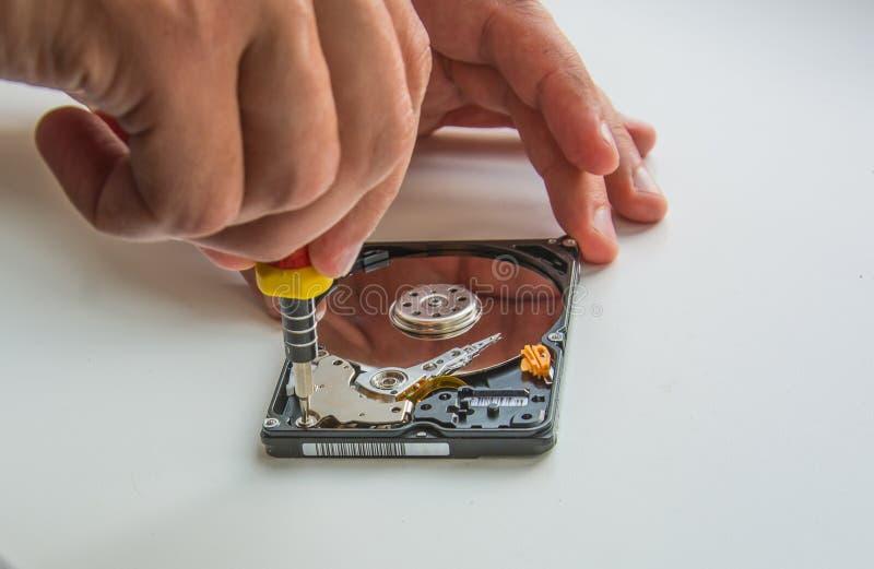 Duas mãos do homem que fixam o disco duro usando a chave de fenda, close-up fotografia de stock royalty free