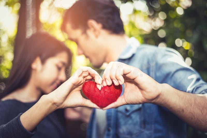Duas mãos dos amantes ou dos pares novos que guardam o fio vermelho do coração no meio no fundo exterior natural para o dia de Va imagens de stock royalty free
