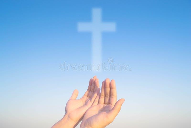 Duas mãos e cruzes de christ e de crentes imagens de stock