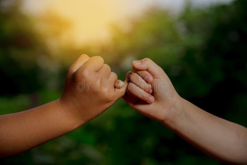Duas mãos engancham-se o ` s pouco conceito do dedo da promessa imagens de stock