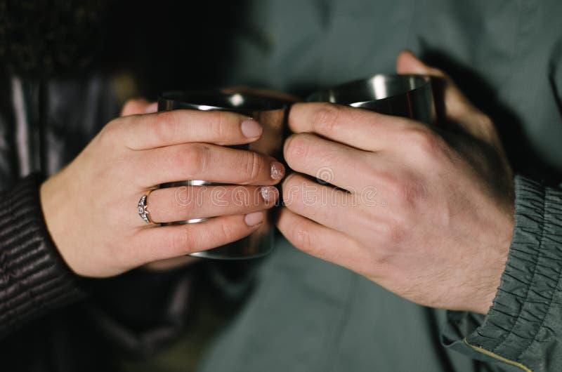 Duas mãos estão guardando dois copos imagens de stock royalty free