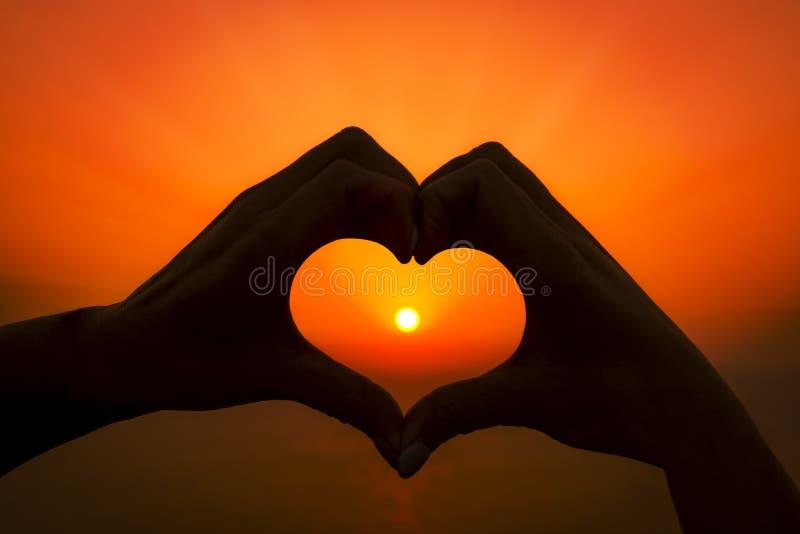 Duas mãos fazem um coração em torno do sol de ajuste em uma ilha grega fotos de stock