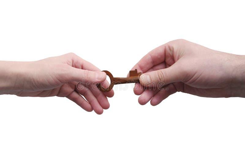 Duas mãos, homem e passagem fêmea a chave velha isolados no fundo branco fotos de stock royalty free