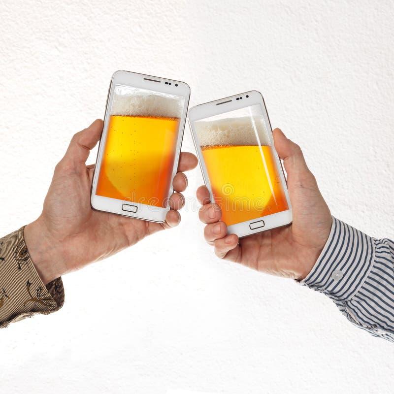 Duas mãos masculinas nas camisas mantêm telefones espertos com cerveja contra o fundo branco imagens de stock