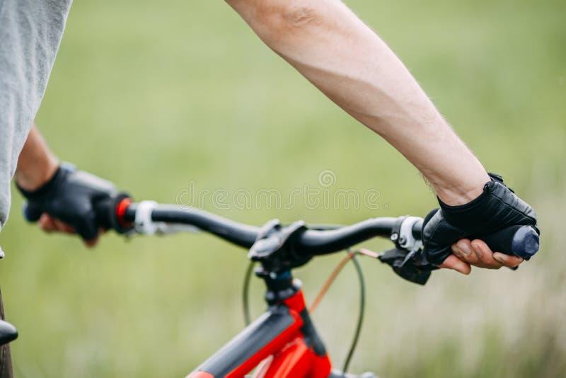 Duas mãos masculinas nas luvas que guardam o guiador da bicicleta fotografia de stock royalty free