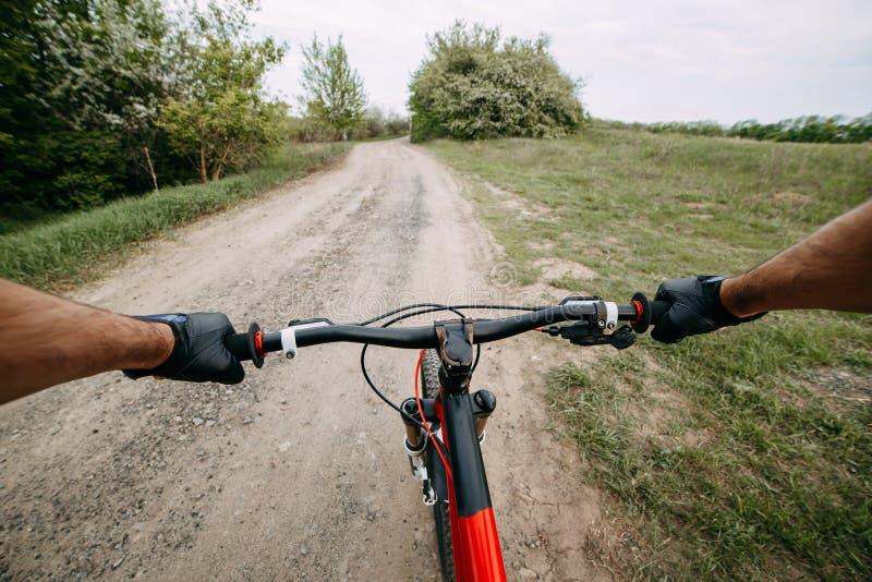 Duas mãos masculinas nas luvas que guardam o guiador da bicicleta imagem de stock