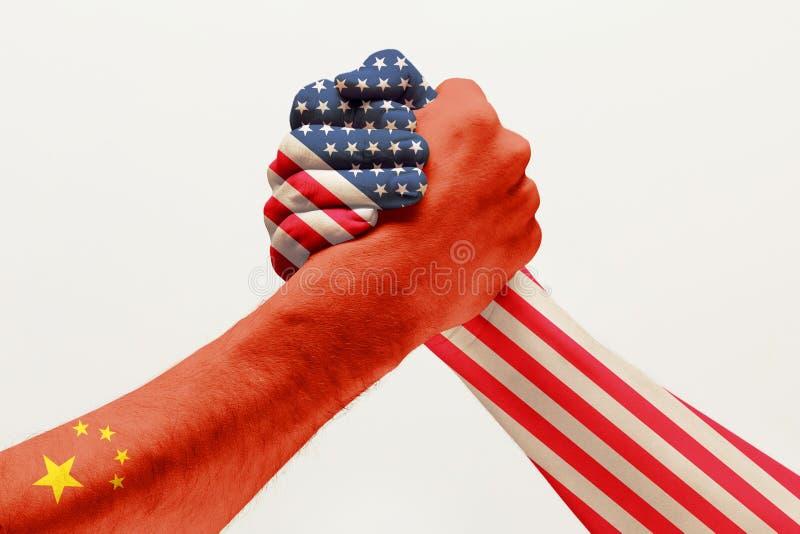 Duas mãos masculinas que competem na luta romana de braço colorida em bandeiras de China e de América fotografia de stock